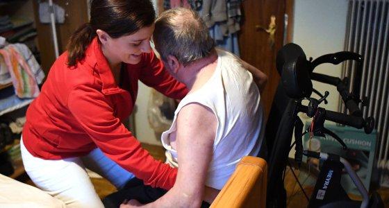 EIne Pflegefachkraft hilft einem Pflegebedürftigen in den Rollstuhl. /dpa