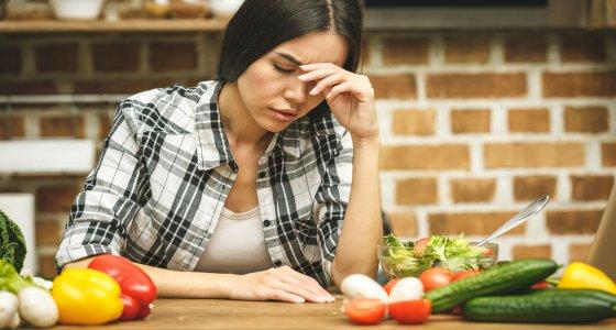 Junge Frau sitzt verzweifelt vor einem Tisch voll gesunder Lebensmittel. /denis_vermenko, stock.adobe.com