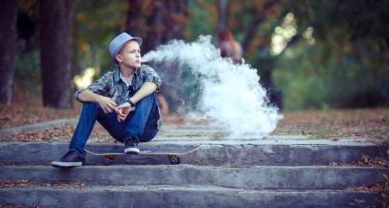 Jugendlicher sitzt auf einer Treppe mit seinem Skateboard und inhaliert eine E-Zigarette/6okean, stock.adobe.com
