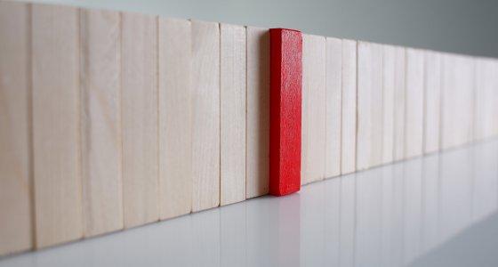 Eine Reihe von Holzstäben in Naturfarben werden unterbrochen von einem roten Holzstab. /Анна Купревич, stock.adobe.com