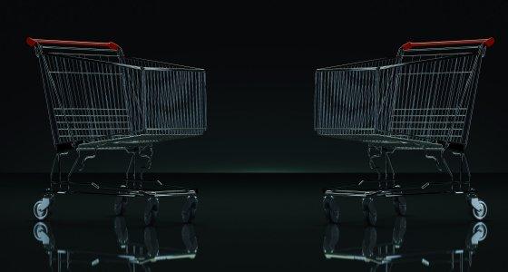 Zwei Einkaufswägen vor schwarzen Hintergrund. /lchumpitaz, stock.adobe.com