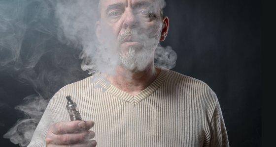 Älterer Mann mit weißem Bart raucht eine E-Zigarette. /Armin Staudt stock.adobe.com