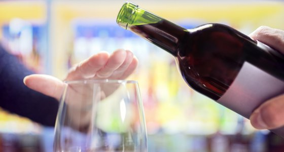 Hand wehrt erneutes Einschenken von Wein in ein Glas ab. /Brian Jackson, stock.adobe.com