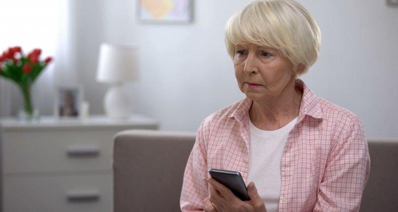 Ältere, einsame Frau hält ihr Smartphone in der Hand. /motortion, stock.adobe.com