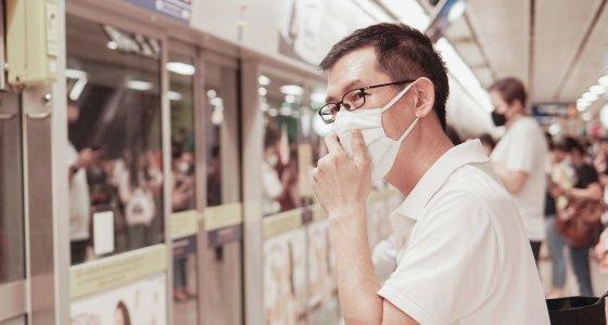 Mann mit Atemmaske steht auf einem Bahngleis mit vielen anderen Menschen. /sewcream, stock.adobe.com
