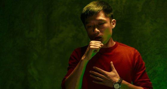 Junger Mann aus Asien hält sich die Hand vor den Mund, um zu husten. /fotofabrika, stock.adobe.com