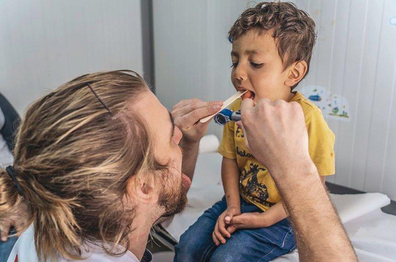 Routine in der Kinderklinik: Ein Arzt von MSF untersucht den vierjährigen Sahel aus dem Flüchtlingslager Moria, der erkältet ist und eine Wunde am Kopf hat. Foto: Anna Pantelia/MSF