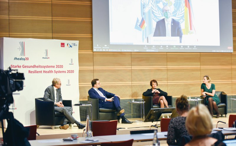 Hybride Konferenz: KBV-Chef Andreas Gassen, Minister Jens Spahn und die Vorsitzende des GKV-Spitzenverbandes, Doris Pfeifer, bei der Konferenz in Berlin. Zugeschaltet aus Kopenhagen ist Hans Kluge von der WHO. Foto: Andrea Katheder