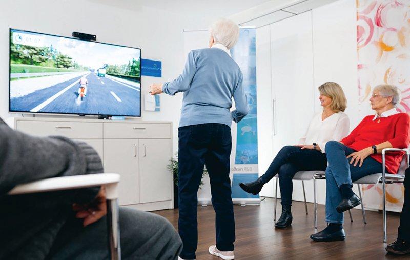 Eine Seniorin steuert ein digitales Motorrad über die Landstraße. Mithilfe der memoreBox, einer Videospielkonsole, die Bewegungen vor dem Bildschirm erfasst, können ältere Menschen ihre mobilen und kognitiven Fähigkeiten stärken. Foto: RetroBrain R&D